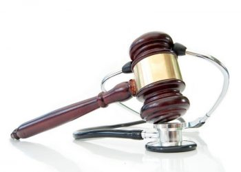 Stethoscope wrapped around a gavel over a white background